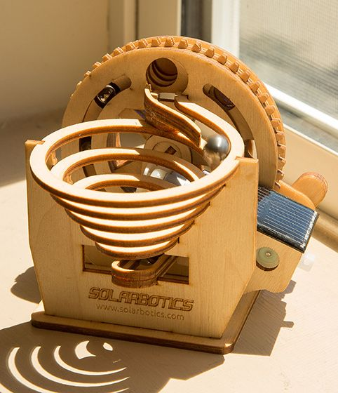 """Wood Marble Machine Kit ($35): """"The circuit takes the light from the solar cell, stores it, and releases it in a pulse, making the gear wheel move, which eventually drops the marble down the spiral."""""""