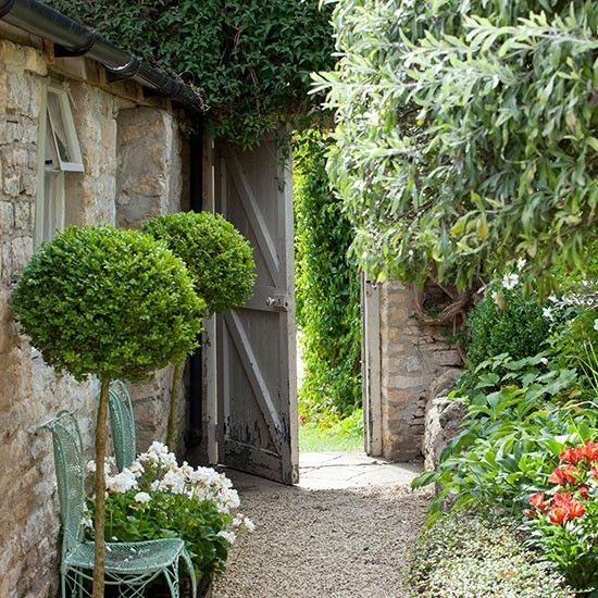 Idea for side entrance to house. Like the idea of gravel paths and borders. Country garden with lollipop hedges and a gravel path