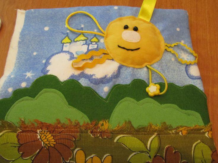 Солнышко забавное и очень мягкое, лучики все из разных материалов, на резиночке пуговка-цветочек. А кустики не простые. Это кармашек для облачка и вкусной конфетки для малыша.