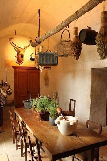 Love this old farmhouse table and hanging baskets above.