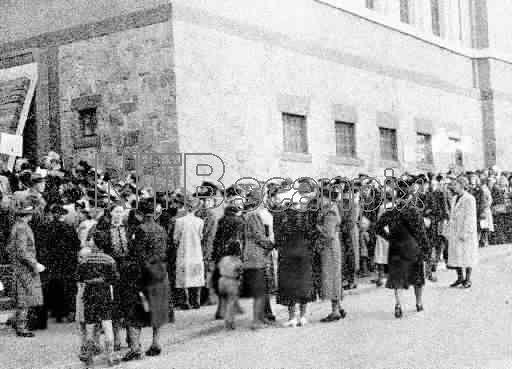 """""""Norge under okkupasjonen, høsten 1944. Varemangel. Kø utenfor Deichmanske bibliotek hvor rasjoneringskortene hentes. Det er matvaremangel og mangel på alt annet, og uten rasjoneringskort er det ingenting å få kjøpt."""""""