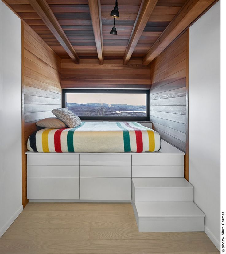 This children's bedroom has a cozy built-in bed that sits above built-in drawers, and is flush with the full-width window.