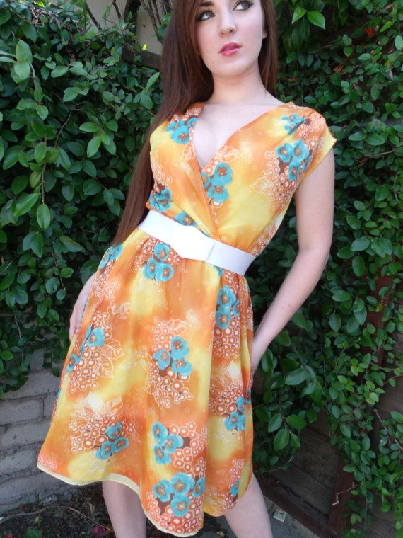 Vintage Day Dress in great condition. Vibrant colors detailed in floral pattern. Deep V Neck. Lined with a solid yellow lining Elastic at the waist ** Belt not included. Approx Size: Large....Big on model who is a 5/6 Measurements: Bust: 40+ in. Waist: Hangs at 32 in.