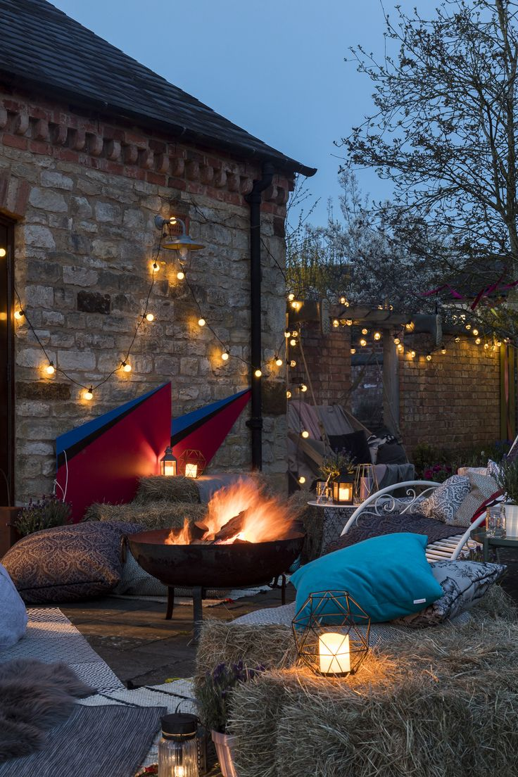 Jo Whiley's Garden - the epitome of home festival style! Complete with fire pit, hay bales, @festivelights, cosy blankets and cushions, it's perfect for Summer nights. Click for more festival season style tips from Jo Whiley.