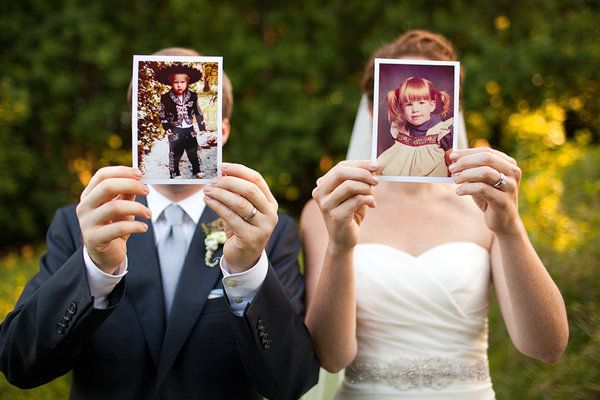 Groom and Bride holding childhood photos of themselves
