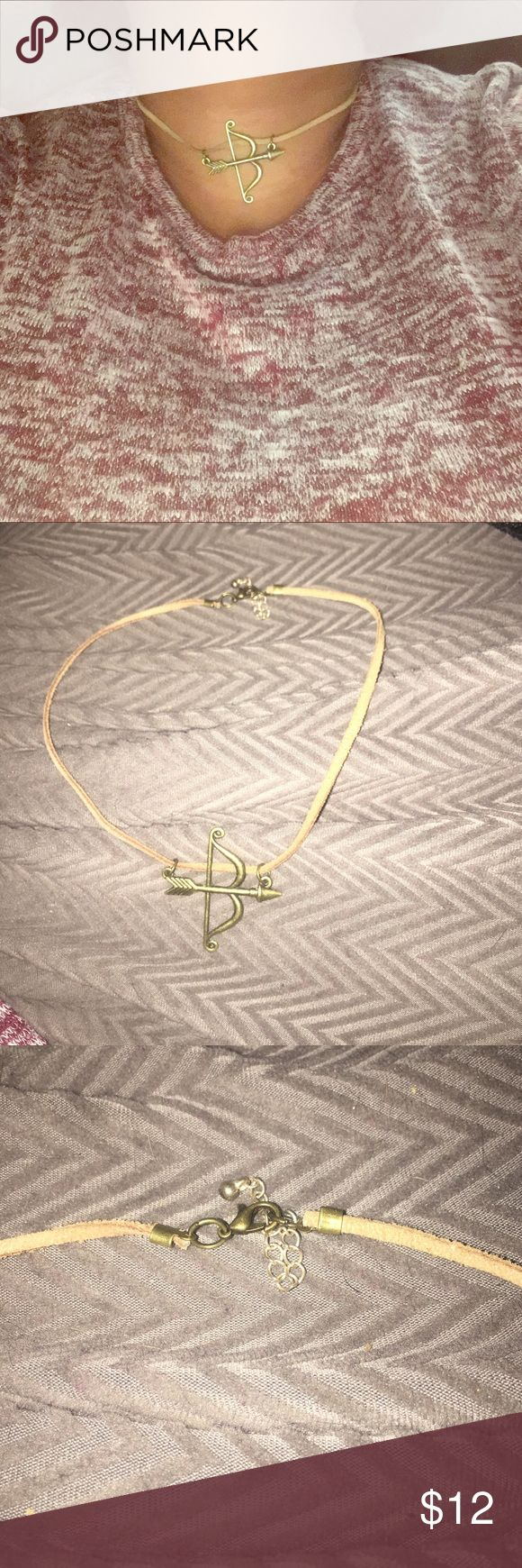 Cute bow & arrow necklace. Cute bow & arrow charm on a simple tan cord. Has lobster clasp closure. Jewelry Necklaces