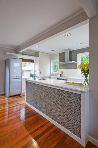 Retro fridge. Tile wall and island. Wood floors.