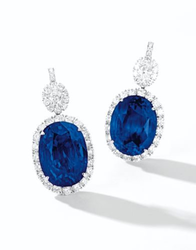 Impressive Pair of Sapphire and Diamond Earrings. Each set with an oval Burmese sapphire weighing 44.11 and 40.11 carats respectively, surrounded by brilliant-cut diamonds, surmounted by an oval diamond framed by brilliant-cut diamonds, the diamonds altogether weighing ~ 6.80 carats, mounted in platinum.
