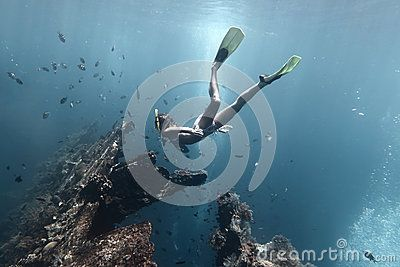 Young woman diving on a breath hold and finning in blue transparent sea near wreck USAT Liberty, Tulamben, Indonesia