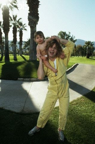 Rock star Ozzy Osbourne plays with his infant child. Palm Springs, December 31, 1984