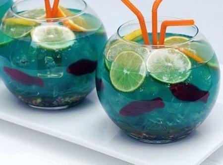 Fish Bowl - vodka, coconut rum, blue curacao, sweet-and-sour mix, pineapple juice, lemon-lime soda, blue food colouring, nerds candy, Swedish fish candy, lemon/lime/orange slices