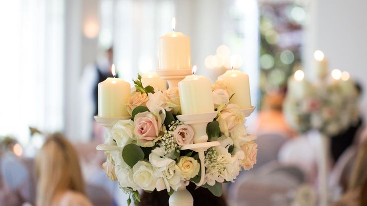 Ivory candelabra with church candles and rings of flowers in ivory, pink and peach