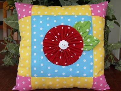 A pretty polka dot pillow with yo yo.