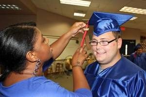 LIFE Academy Vocational Specialist Ketinna Gadsden assists graduate Travis Watt with his mortarboard.    The L.I.F.E. Academy is a Lee County charter school for students with special needs, and graduated a record-size class of eight students this year.    visit http://www.goodwilllifeacademy.org