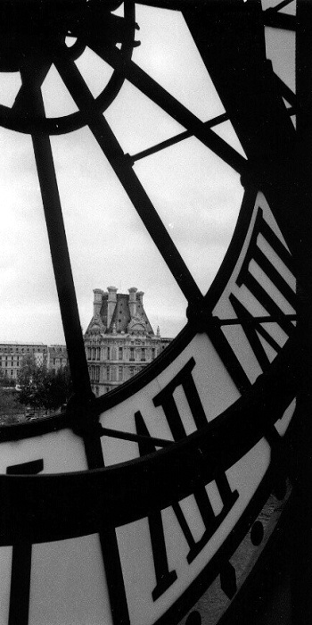 view of the Louvre through Musee D'Orsay clock