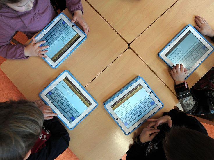 Comment les fabricants de tablettes s'incrustent dans les classes [Des enfants utilisent des iPad dans une école maternelle à Haguenau, le 18 mars 2013 (FREDERICK FLORIN/AFP)]