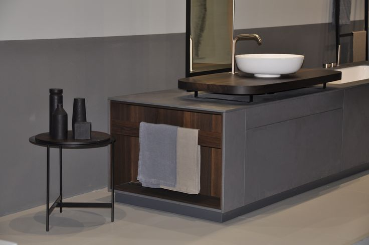 MANHATTAN Bathtub Washbasin system is characterized by practical open racks in smoked oak on both sides. Also displayed: MATERIAL TABLE, our contemporary version of the small table with varnished steel frame and smoked oak surface.