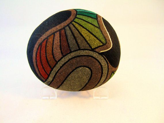 One of a kind hand painted rocks art, signed dated and numbered art, rainbow colors abstract art designs outlined with black and accents of gold. Collectibles. Unique gifts for home decor and office decor. This fantastic 3D art is wonderful gifts for her or gifts for him for a rustic decor accessory. This rock can be rotated in different directions to present a variety of faces, as your mood dictates. The photographs show the front side and the back side, of the stone, and a few of the…