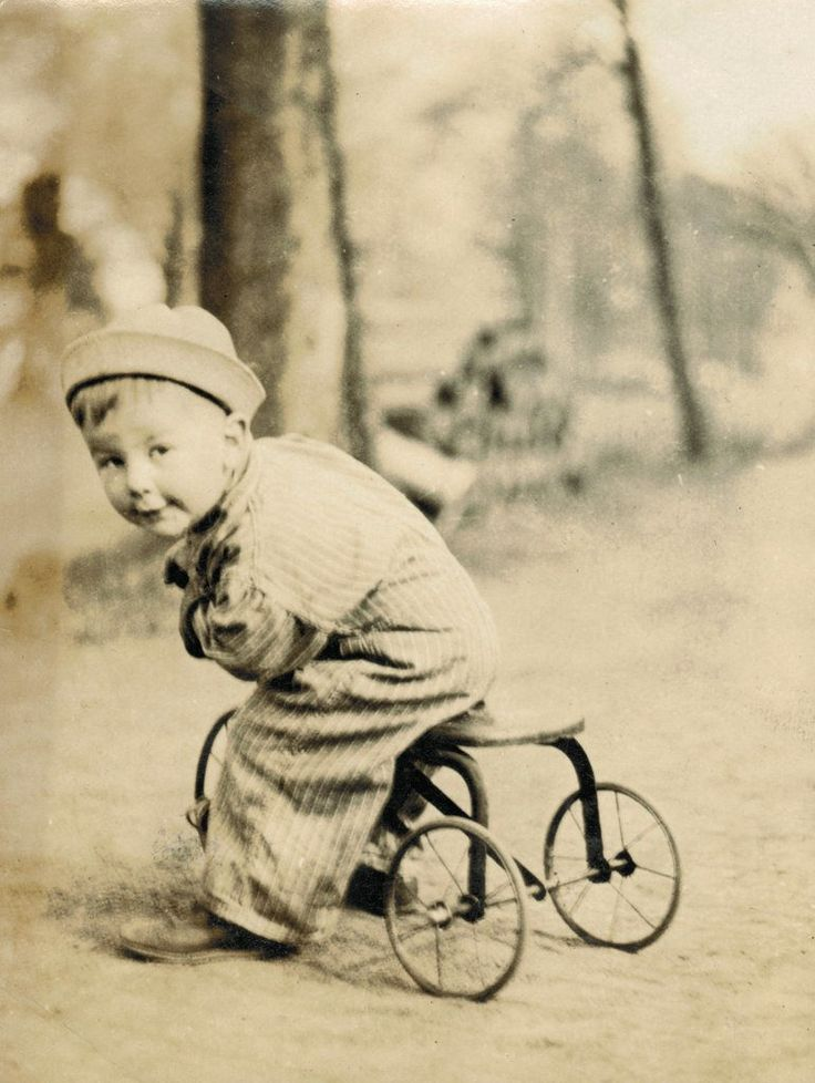 Antique photo of a child on his tricycle.
