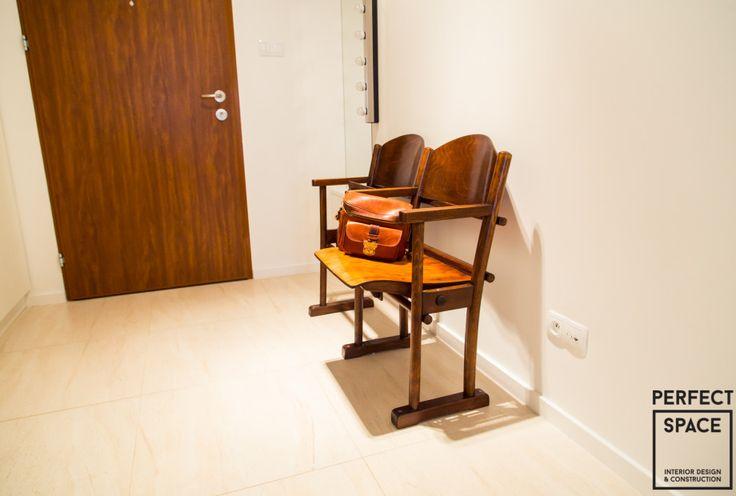Aranżacja przedpokoju z oryginalnymi drewnianymi fotelami kinowymi, które służą jako siedzisko.