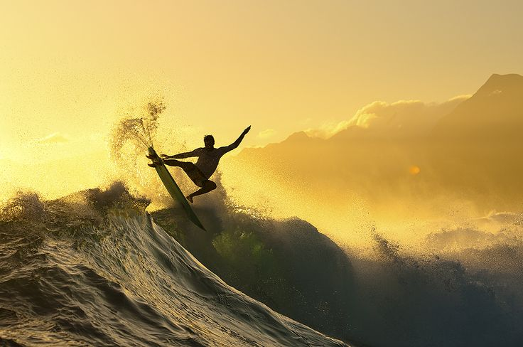 """In a land famous for its monster of a left, a few lesser-known rights can provide a more playful experience. """"Dan Malloy finds a moment of illumination between the setting sun and the towering Tahitian islands,"""" says Chris. Photo: Burkard"""