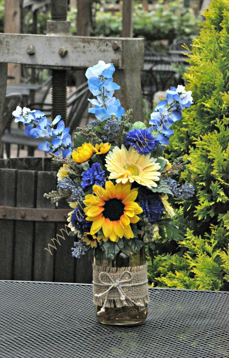 Rustic-style centerpiece featuring sunflowers, blue delphinium, blue pom poms, and gerbera daisies in a yellow-tinted mason jar tied with burlap and twine