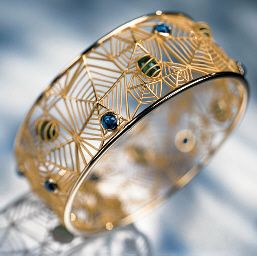 AN EMERALD, SAPPHIRE AND 18K GOLD BANGLE, BY CARRERA Y CARRERA   Designed as a series of gold spider's webs enhanced by cabochon emeralds and sapphires, 6.3 cm. diameter, in a Carrera y Carrera black leather fitted case  Designed by Anne Baus-Valton, signed CC for Carrera y Carrera, no. 260475