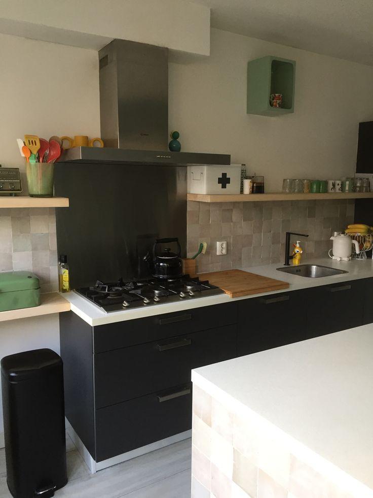 Keuken zwart wit. Zelliges op de muur en op zijkant keukeneiland. Keuken planken hout.