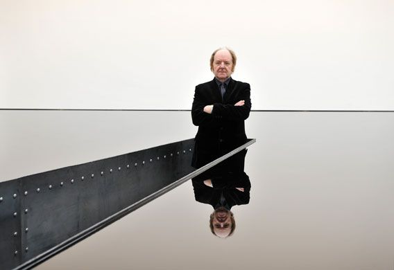 The artist Richard Wilson poses with his installation, a vast tank made out of sheet metal and filled to the brim with thick sump oil