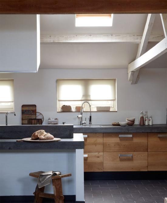 cocina con encimera microcemento, muebles madera acabado natural, ventana en el techo y vigas vistas pintadas de blanco