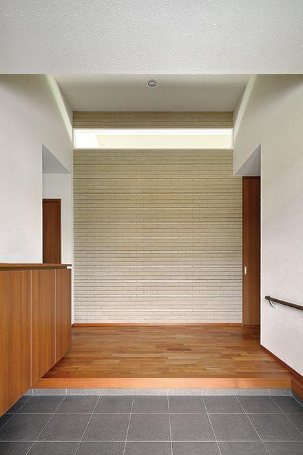 正面に大きなタイル張りの壁を設けた玄関