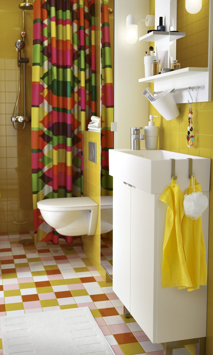 a colorful bathroom with a white wash stand and mirror yellow towels and a shower curtain with hexagon pattern in yellow green orange and pink