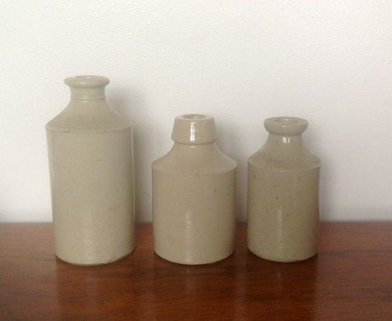 Three pale creamy grey stoneware bottles from the early 20th century, great for adding to shabby chic/ rustic decor.  Larger bottle is 6 tall by 2.5 diameter., this one has 3 small chips on the rim ,neck and base ( see photos )  Medium bottle is 4.7 tall by 2.6 diameter, in very good condition.  Smaller bottle is 4.5 tall by 2.2 diameter and is in good condition with no chips or cracks...it has different colour marks in places. ( see photos )  Please study the pictures, I have tried to show…