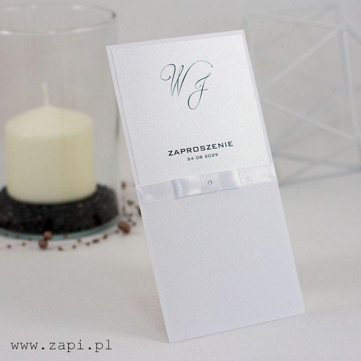 Jednokartkowe zaproszenie ślubne łączące śnieżnobiałą z diamentową bielą. Dekorację stanowi satynowa tasiemka z aplikacją.