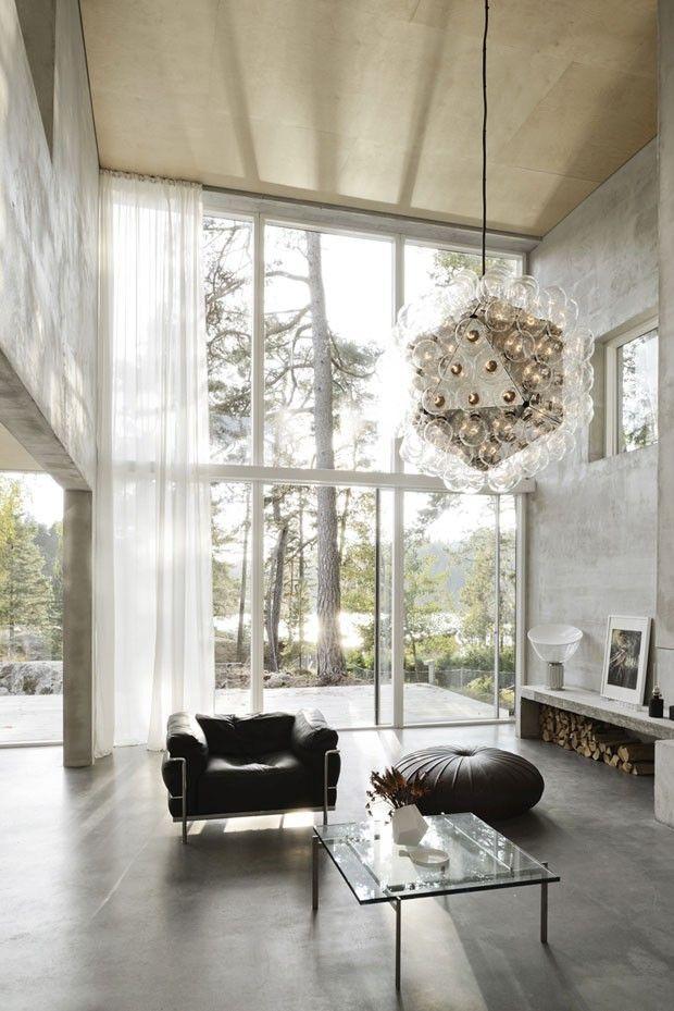 Sala de estar com janela piso-teto, pé direito alto, cimento batino e poltrona preta
