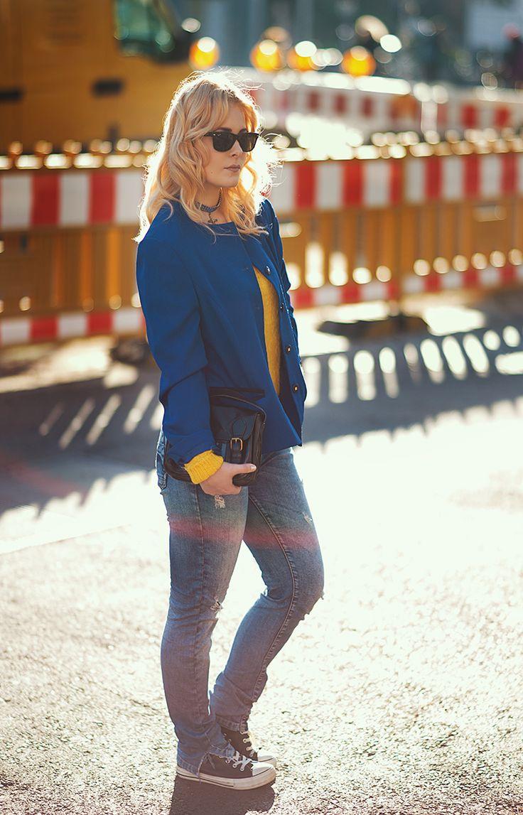 Christina Key trägt eine hellblaue Jeans im used Look, einen zitronen-gelben Pullover, eine royalblaue Jacke und ihre blonden Haare wellig.