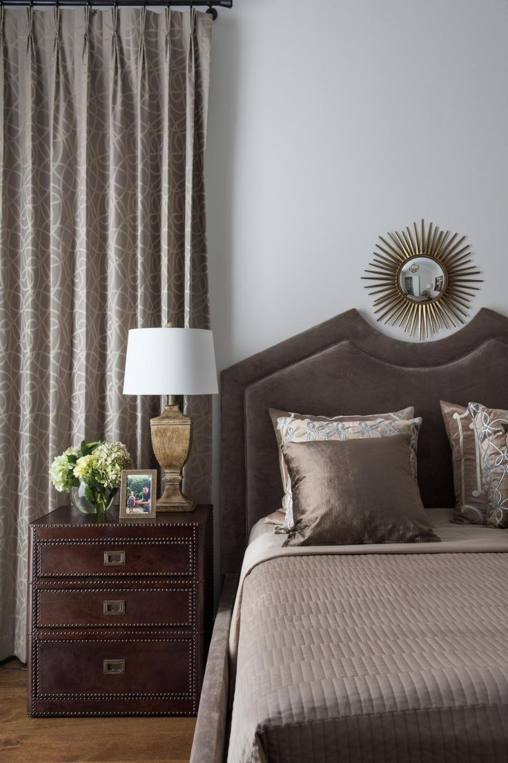 This stylish bedroom features a taupe leather bed frame and headboard with matching bed linens and metallic throw pillows. A leather studded nightstand with a small metal lamp is positioned in front of a window trimmed in floor-length patterned curtains. A metal starburst mirror hangs above the bed.