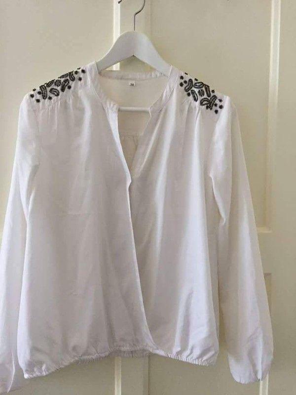 Nieuwe blouse wit met zwarte glitter pailletten op de schouders
