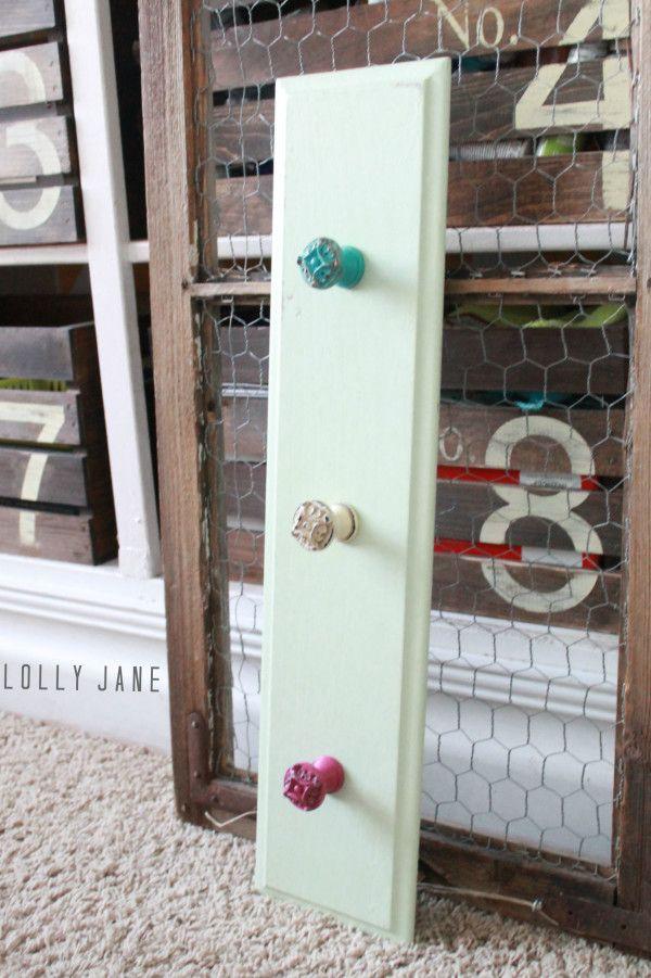 Make cute hooks by screwing fun knobs into a repainted cupboard door, easy! #diy #hooks #knobs