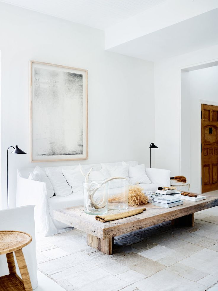 White living living room with low rustic wood coff…