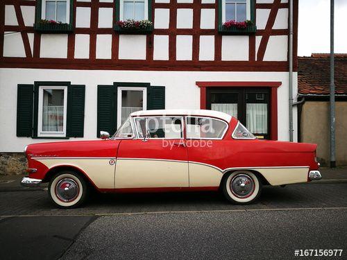Zweitürige Opel Rekord P1 Limousine der Fünfzigerjahre mit traditioneller Zweifarbenlackierung vor einem Fachwerkhaus in Wettenberg Krofdorf-Gleiberg in Hessen
