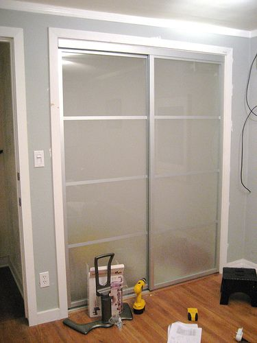 Horrible mirrored closet doors replaced with plexiglass and hit with a sander to create a frosted glass effect. Brilliant