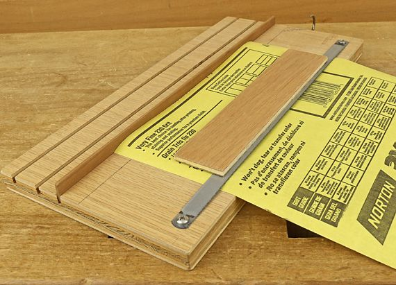 Sandpaper cutter - The sheet cutter makes it almost fun to size sandpaper. A hacksaw blade is screwed to a piece of plywood with enough slack to permit the sheet to easily fit under. A piece of thin plywood is glued to the blade to make it easy to press the blade firmly onto the back of the paper prior to tearing it. A slat is placed in one of the table-sawn kerfs that provide the right width. The most common are 1/3 sheets made by cutting across the narrow width of one sheet.