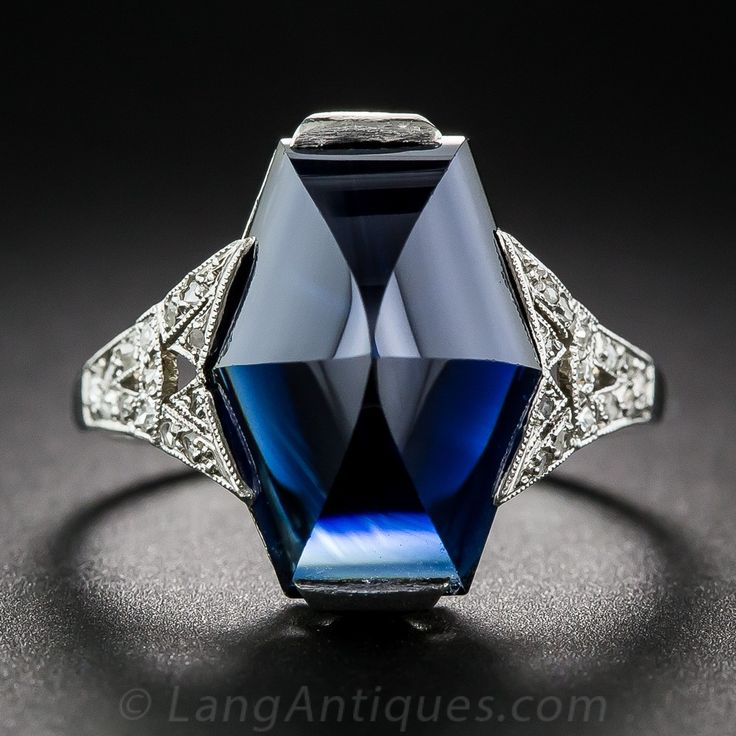 This striking French made ring, circa 1925, features a very special gemstone: a 7.25 carat sapphire fashioned into a faceted hexagonal buff-top cut. The dark midnight blue gemstone is presented in a gorgeous mounting, hand crafted in platinum with tiny single-cut and rose-cut diamonds glittering on each shoulder. The singular and sensational original Art Deco jewel measures just a tad shy of 5/8 inch. French hallmarks outside of the ring shank, numbered inside. Currently ring size 5 1/2.