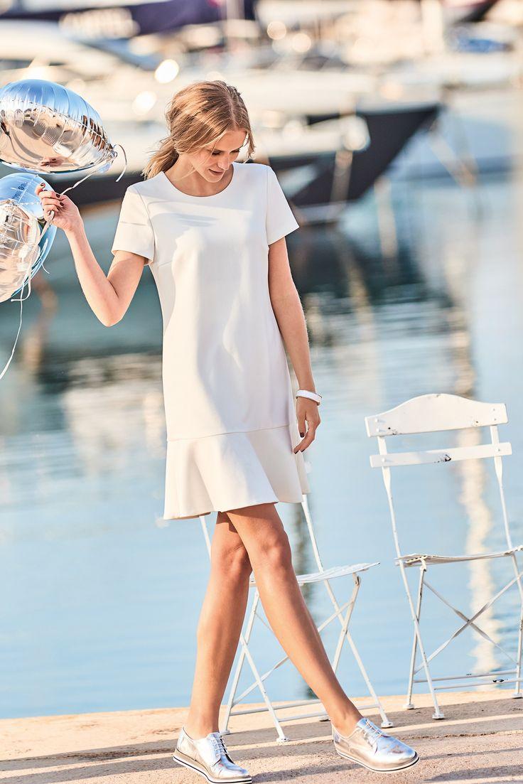 Clean and chic: Mit schlichter Schönheit begeistert das weiße Kurzarmkleid von OUI mit geradem Schnitt und breitem, angesetztem Volantsaum.
