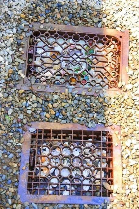 Vintage floor grates in the garden path. I like the idea of adding a solar light and brightly colored stones underneath.