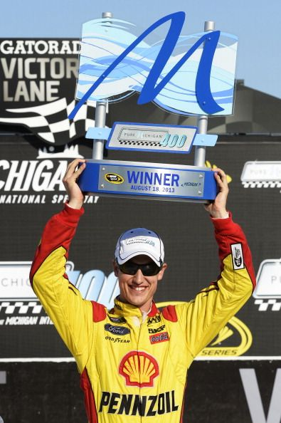 BROOKLYN, MI - AUGUST 18: Joey Logano, driver of the #22 Shell-Pennzoil Ford, celebrates the trophy in Victory Lane after winning the NASCAR Sprint Cup Series 44th Annual Pure Michigan 400 at Michigan International Speedway on August 18, 2013 in Brooklyn, Michigan. (Photo by John Harrelson/Getty Images)