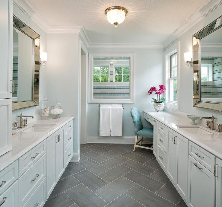exquisite blue and gray master bathroom features facing pale blue washstands separated by slate herringbone floor tiles and accented with polished nickel
