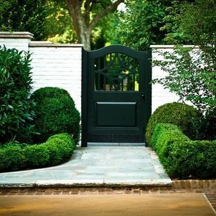 gate door entry change to red brick wall with boxwood hedge
