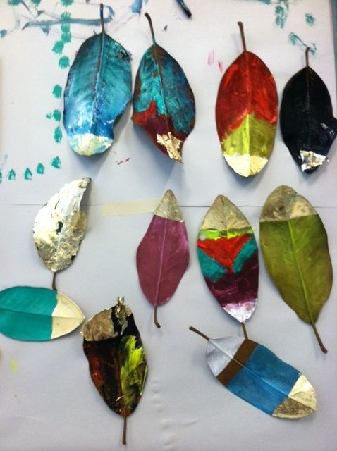 Painting leaves with acrylic paint, touches of gold leaf and glitter.
